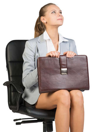 half turn: Businesswoman on office chair, looking upwards to her left, holding suitcase on her knees. Isolated over white background Stock Photo