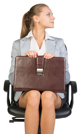 Businesswoman on office chair, her head turned to her left, holding suitcase on her knees. Isolated over white background photo