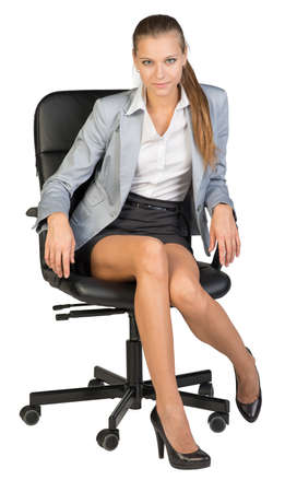Businesswoman sitting on office chair with one foot on toe, looking at camera. Isolated over white background