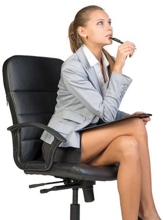 Businesswoman sitting on office chair, holding pen at her chin and clipboard on her knees, with a thinking expression on her face. Isolated over white background Stock Photo