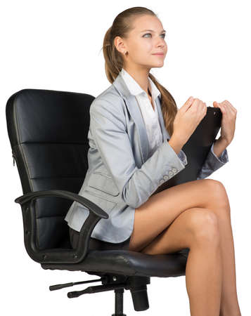 half turn: Businesswoman sitting on office chair with clipboard in hands, looking ahead. Isolated over white background Stock Photo