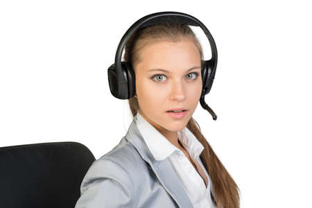 Businesswoman in headset sitting on chair, her lips parted, looking at camera. Isolated over white background photo
