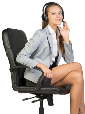 half turn: Businesswoman in headset sitting on office chair, with her fingers on microphone boom, looking at camera, smiling. Isolated over white background Stock Photo