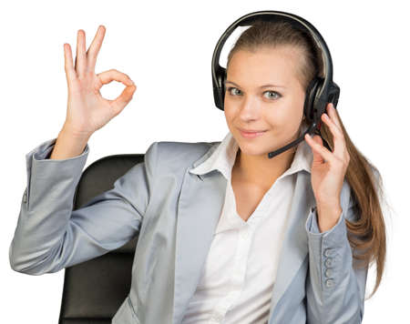all right: Businesswoman in headset making okay gesture, her other hand on headset speaker, looking at camera, smiling. Isolated over white background
