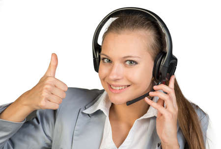Businesswoman in headset showing thumb up, her other hand on microphone boom, looking at camera, smiling. Isolated over white background photo