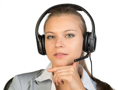 Businesswoman in headset sitting on chair, hand under chin, lips parted, looking at camera. Isolated over white background photo