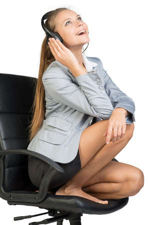 Businesswoman in headset sitting on office chair with legs, looking upwards, laughing. Isolated over white background Stock Photo