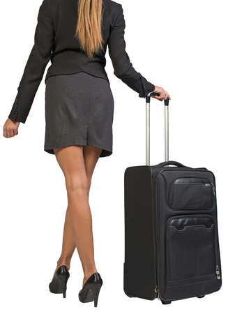 Cropped image of businesswoman with wheeled travel bag makes step forward, back view. Isolated over white background photo