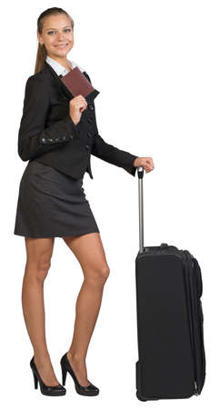 Businesswoman with wheeled travel bag, showing passport with blank cover, looking at camera. Isolated over white background photo
