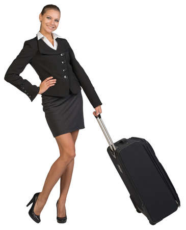 Businesswoman holding wheeled bag, hand on hip, looking at camera, smiling. Isolated over white background photo