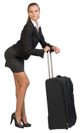 Businesswoman bending forward leaning on extended handle of wheeled suitcase, looking at camera. Isolated over white background photo