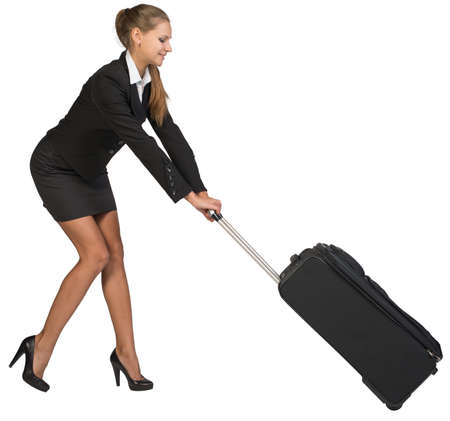 Businesswoman dragging heavy wheeled suitcase at utmost strain. Isolated over white background photo