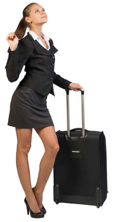 Businesswoman with wheeled suitcase, holding her hair with other hand, looking upwards. Isolated over white background photo