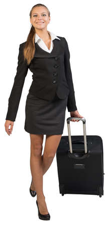Businesswoman walking with wheeled suitcase, looking at camera, smiling. Isolated over white background photo