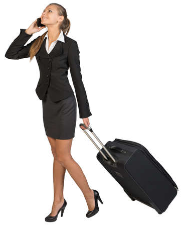 Businesswoman walking with wheeled suitcase, talking on the phone, smiling. Isolated over white background photo