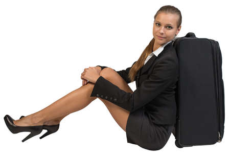 hugging knees: Businesswoman sitting next to side view suitcase, hugging her knees, looking at camera. Isolated over white background