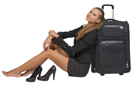 Businesswoman with her shoes off sitting next to front view suitcase with extended handle, looking at camera. Isolated over white background photo