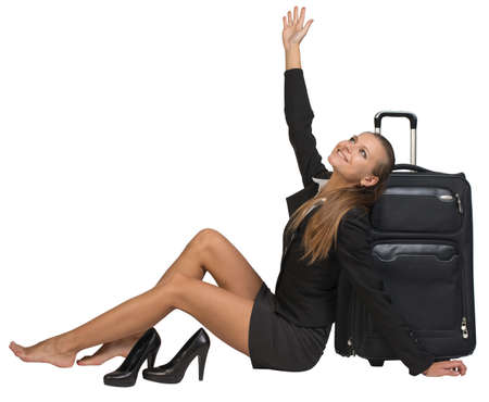 Businesswoman with her shoes off sitting next to front view suitcase with extended handle, her hand stretched upwards, looking upwards. Isolated over white background photo