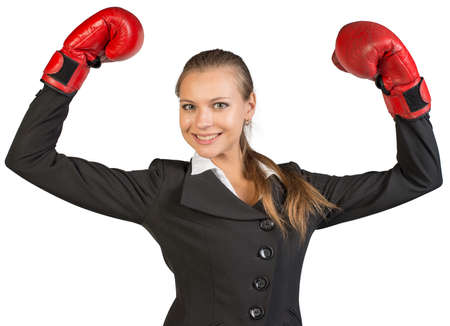 Businesswoman wearing boxing gloves standing in victory pose, looking at camera, smiling. Isolated over white background photo