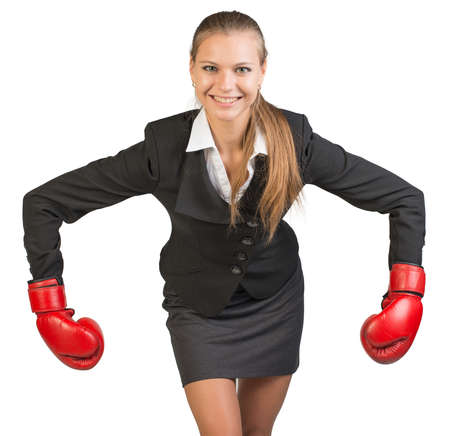 Businesswoman wearing boxing gloves bending forward with her arms bent and outstretched, looking at camera, smiling. Isolated over white background photo