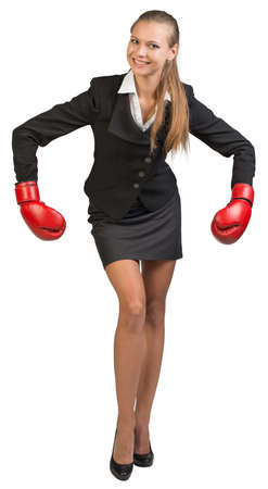 Businesswoman wearing boxing gloves bending forward with her arms forward down, looking at camera, smiling. Isolated over white background photo