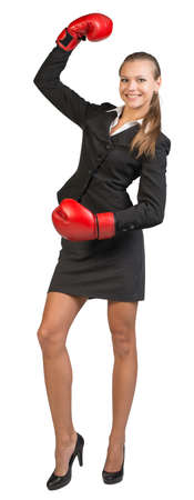 muffle: Businesswoman wearing boxing gloves standing with one hand raised, looking at camera, smiling. Isolated over white background Stock Photo