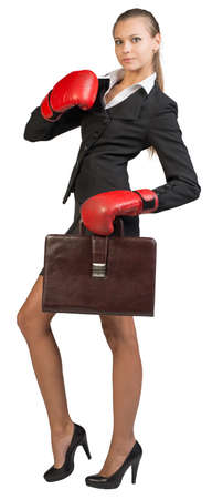 to muffle: Businesswoman wearing boxing gloves holding briefcase, looking at camera. Isolated over white background Stock Photo
