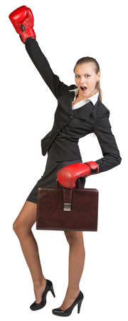 Businesswoman wearing boxing gloves, holding briefcase, with the other hand raised, looking at camera, shouting. Isolated over white background photo