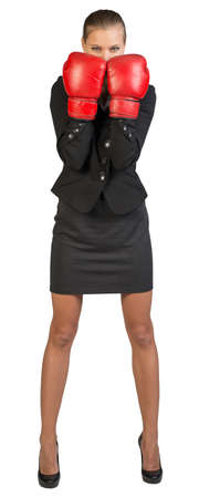 Businesswoman wearing boxing gloves standing in boxing stance, looking at camera. Isolated over white background photo