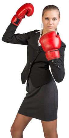 muffle: Businesswoman wearing boxing gloves standing in boxing stance, looking at camera. Isolated over white background Stock Photo