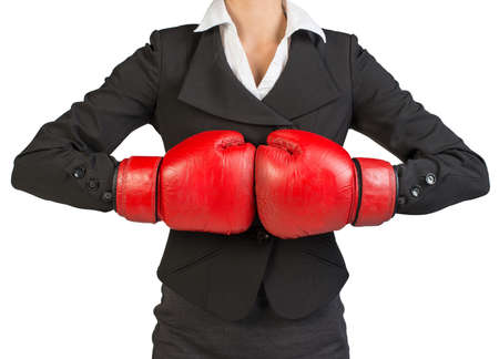 to muffle: Cropped image of businesswoman in boxing gloves holding fist to fist. Isolated over white background