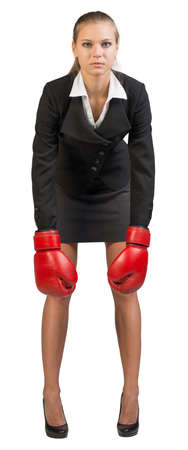 leaning forward: Businesswoman wearing boxing gloves, leaning forward with her hands down, looking at camera. Isolated over white background