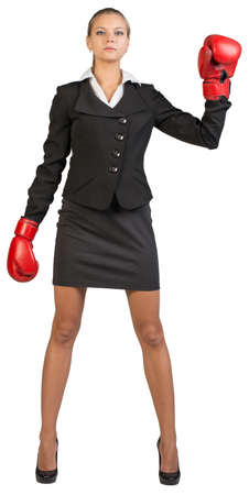 to muffle: Businesswoman wearing boxing gloves, standing feet apart with one arm up, looking at camera. Isolated over white background