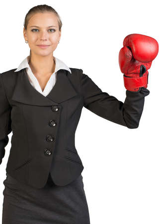 Cropped image of businesswoman wearing boxing gloves with one arm up, looking at camera. Isolated over white background photo