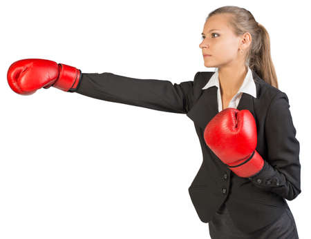 half turn: Businesswoman wearing boxing gloves punching. Isolated over white background
