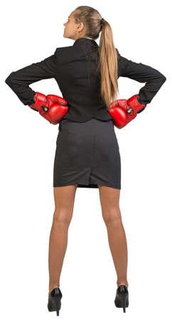mani sui fianchi: Imprenditrice indossando guantoni da boxe sui fianchi in piedi, guardando alla sua sinistra. Isolato su sfondo bianco