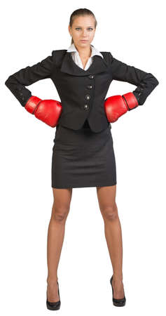 mani sui fianchi: Businesswoman wearing boxing gloves standing akimbo, looking at camera. Isolated over white background