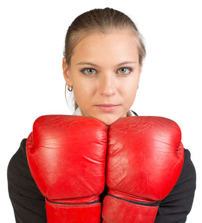 to muffle: Businesswoman wearing boxing gloves holding them together under her chin, looking at camera. Isolated over white background