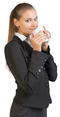 half turn: Businesswoman holding mug at her mouth, looking at camera, smiling. Isolated over white background Stock Photo