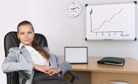 Businesswoman in her office, back in armchair, with her hands clasped over her stomach, looking at camera. Beside are graph showing growth, empty frame, folder, wall clock