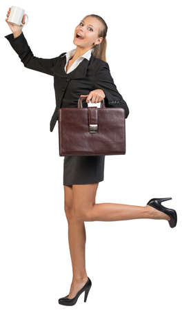 Businesswoman with white mug and briefcase, expressing rapture, looking at camera. Isolated over white background photo