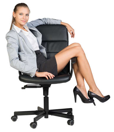 half turn: Businesswoman on office chair with her legs over armrest, looking at camera. Isolated over white background Stock Photo