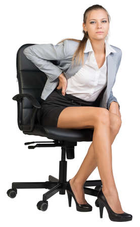 Businesswoman with lower back pain from sitting on office chair, looking at camera. Isolated over white background photo
