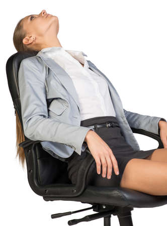 lean back: Businesswoman resting in office chair with her head thrown back, her eyes opened, her arms on armrests. Isolated over white background