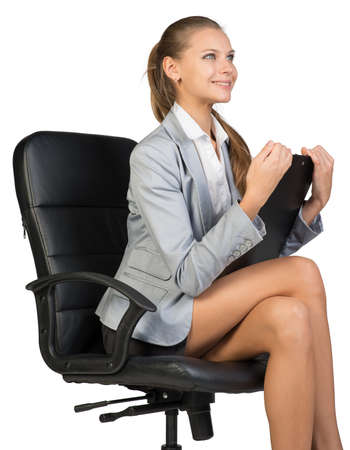 looking ahead: Businesswoman sitting on office chair with clipboard in hands, looking ahead, smiling. Isolated over white background Stock Photo