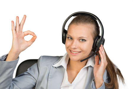 Businesswoman in headset making okay gesture, her other hand on headset speaker, looking at camera, smiling. Isolated over white background photo