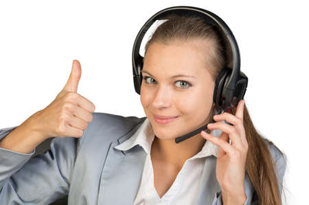 all right: Businesswoman in headset showing thumb up, her other hand on microphone boom, looking at camera, smiling. Isolated over white background