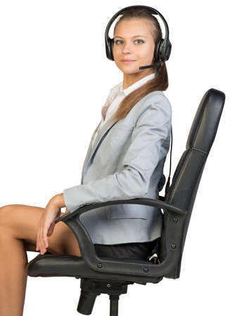 half turn: Businesswoman in headset sitting on office chair, her head half-turned to camera, looking at camera. Isolated over white background Stock Photo