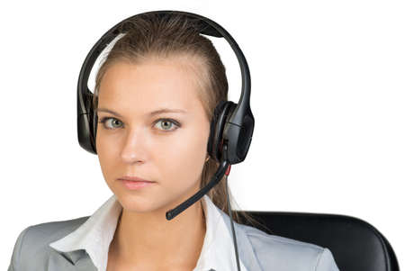 unemotional: Businesswoman in headset looking at camera. Isolated over white background