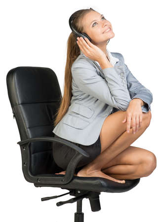Businesswoman in headset sitting on office chair with legs, looking upwards, smiling. Isolated over white background
